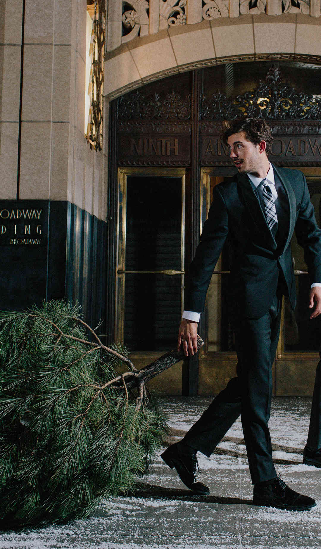 Attractive man wearing a tuxedo dragging a pine tree with his friend