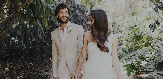 attractive couple in a jungle wearing light outfits and eyeing each other on their wedding day