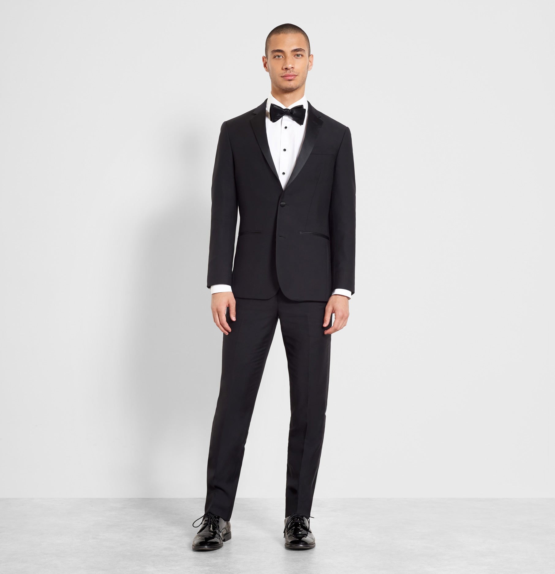 2bc69399fa8 Sleek onyx accessories add visual interest to a timeless notch lapel tux  (worn with the essential butterfly bow tie ...